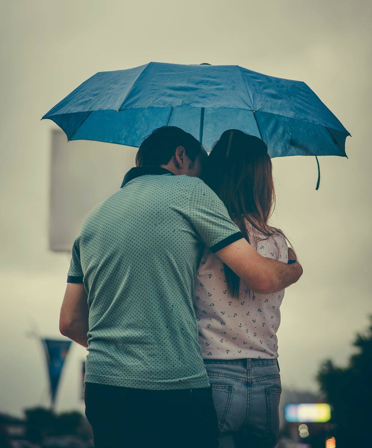 man holds woman as they stand under the umbrella