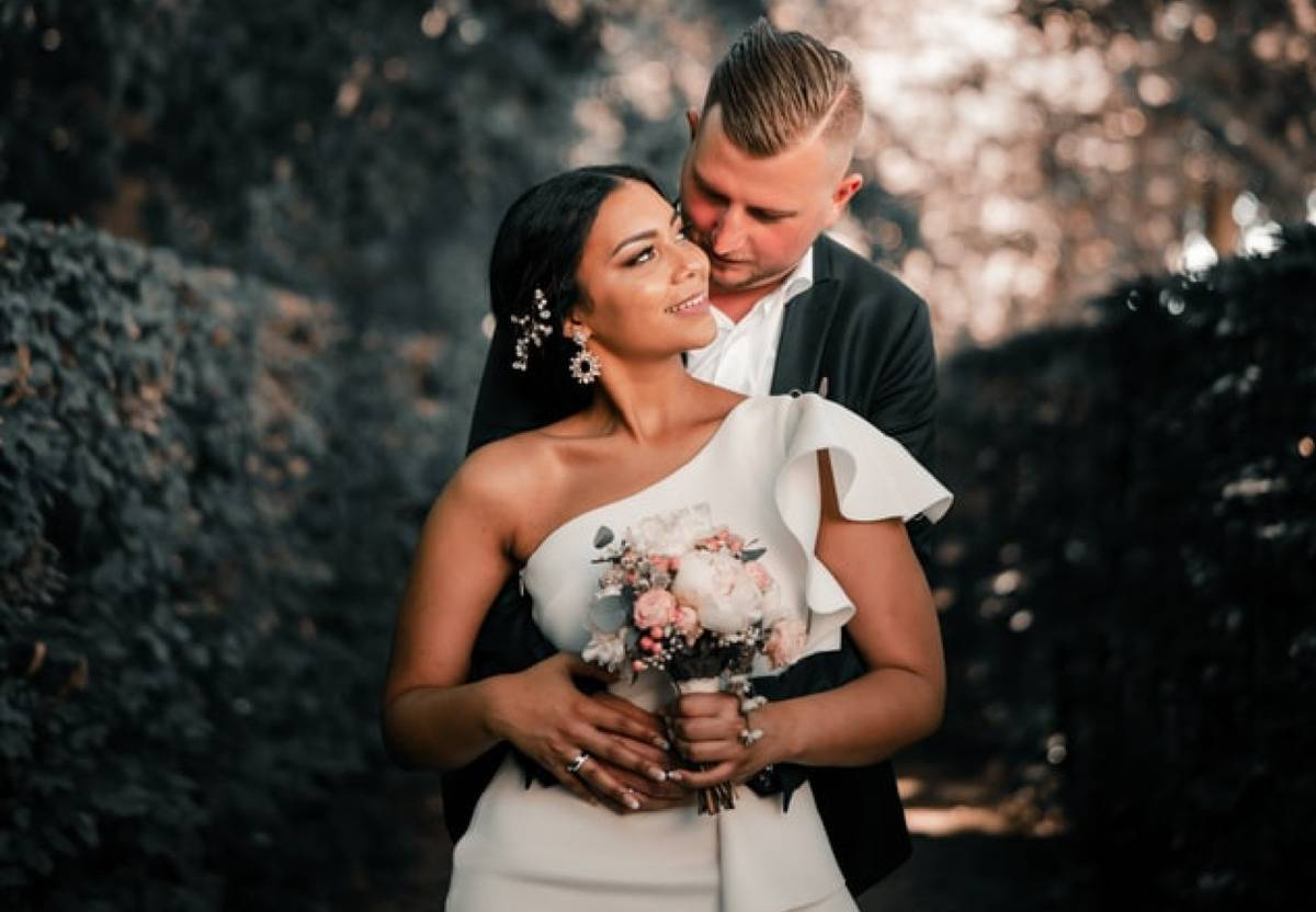 groom holding bride in a prom pose as she looks up at him smiling
