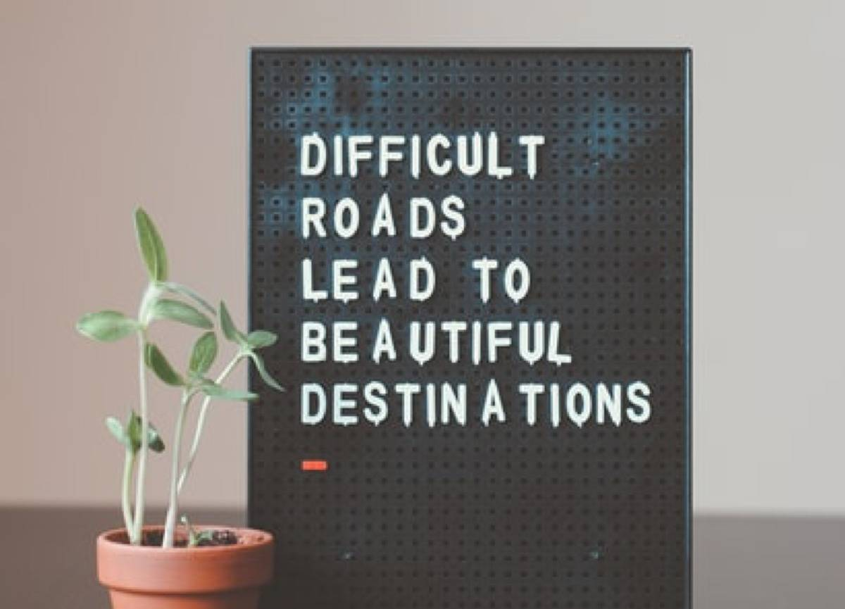 sign that says difficult roads lead to beautiful destinations with a small plant next to it