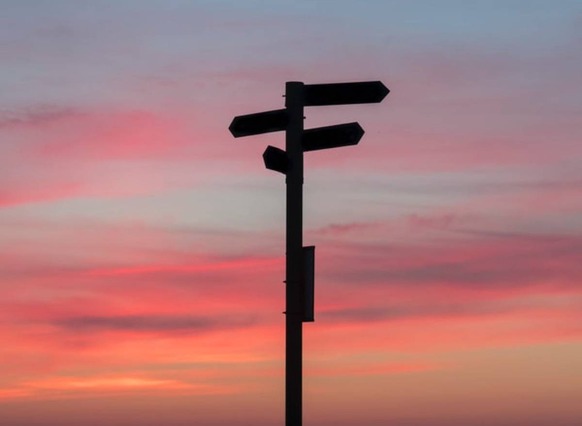 direction sign against sunset