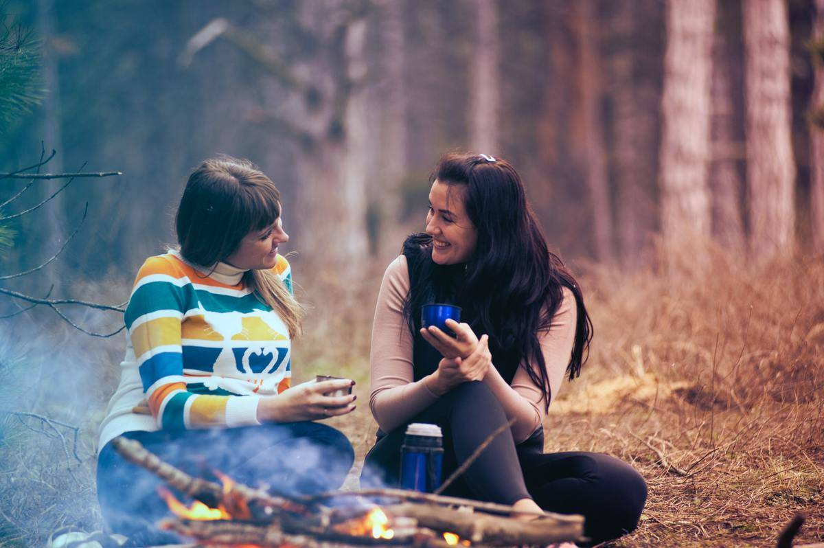 two female friends talking at bonfire