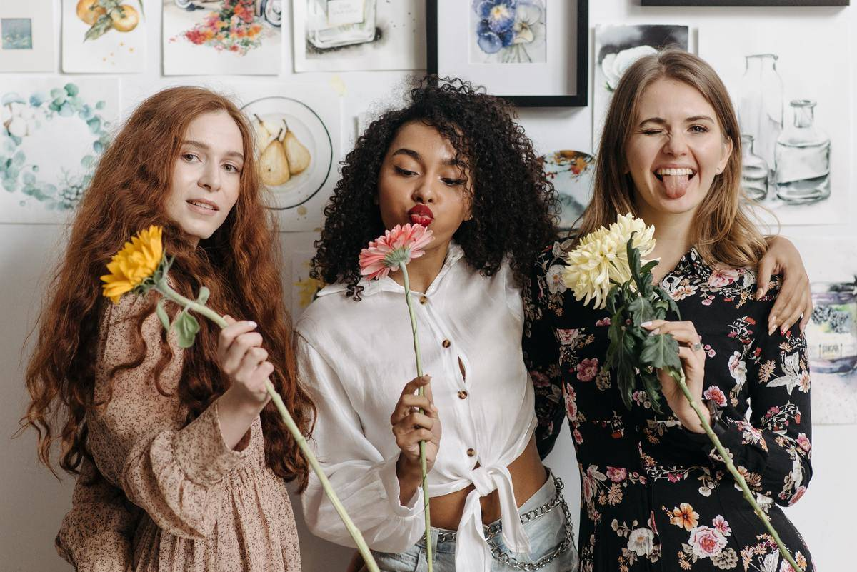 three friends standing in front of a wall of photos holding flowers