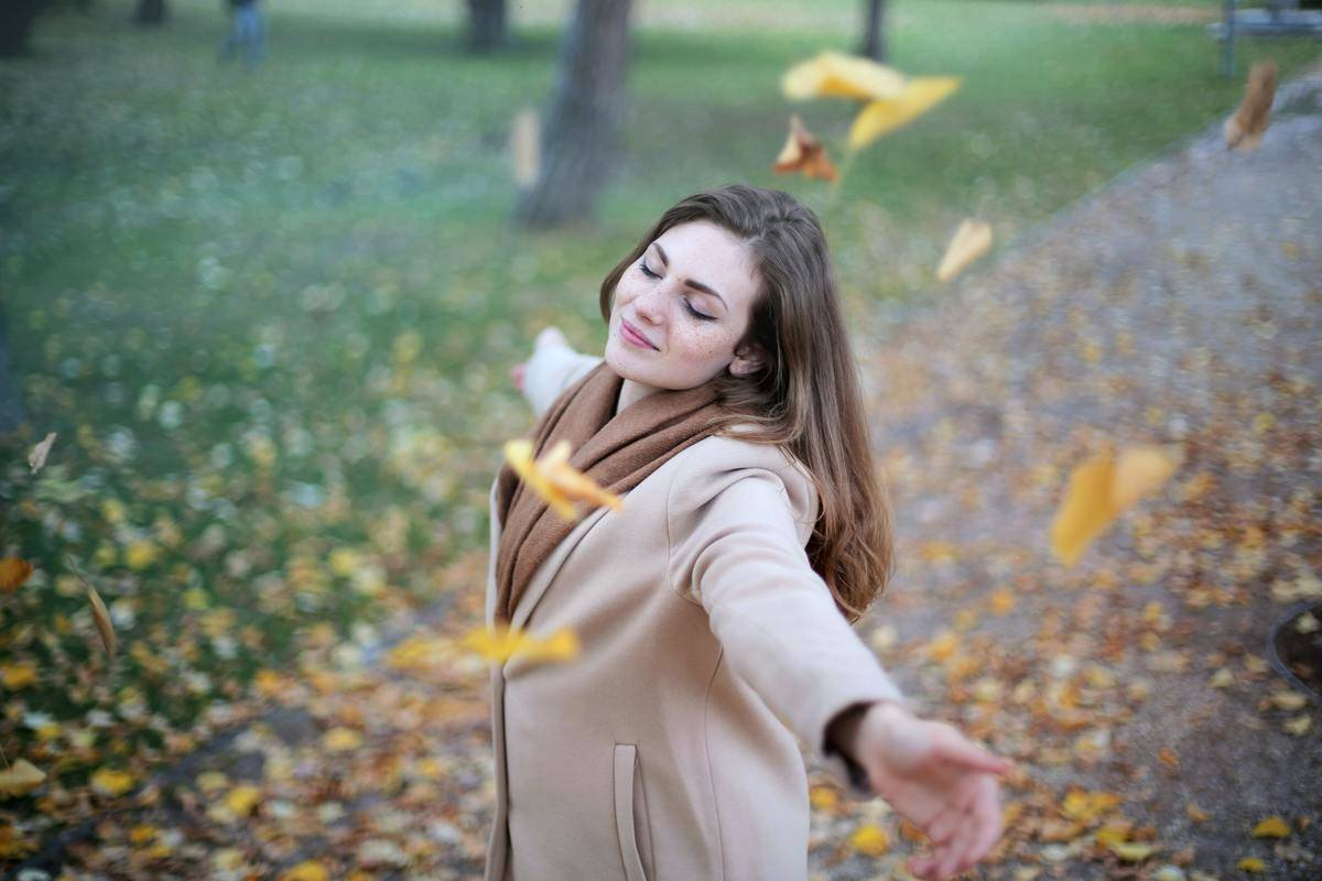 woman standing in a park with her arms outstretched and leaves floating around her