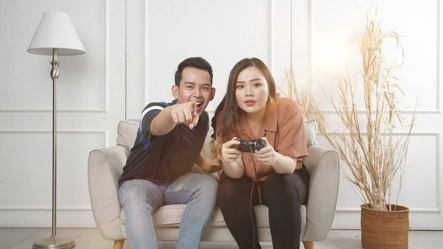 Happy friends playing video games with virtual reality glasses - Young couple having fun with new technology console online
