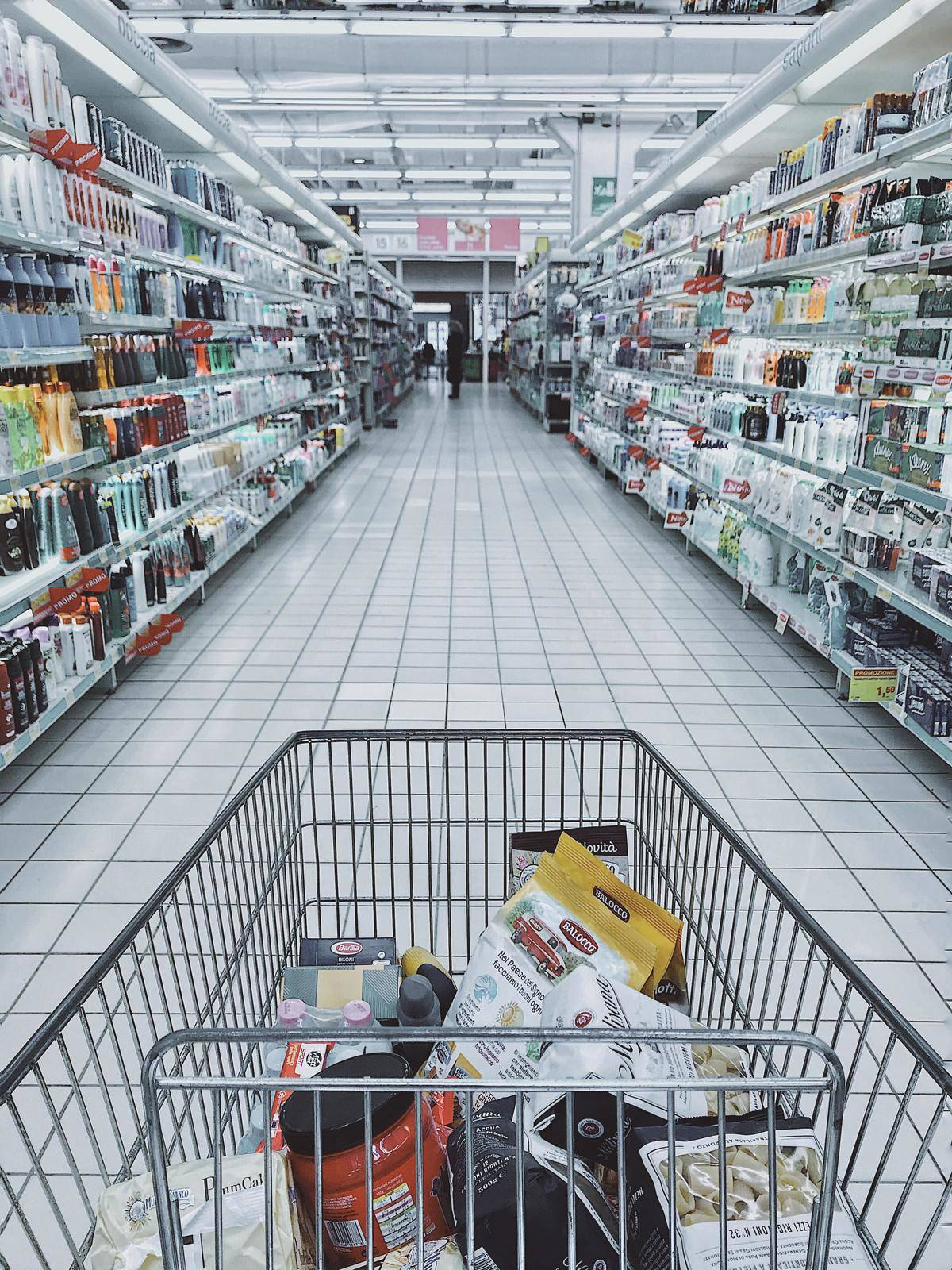 cart with items inside going down grocery aisle