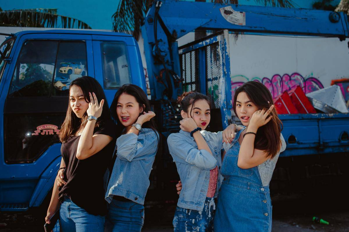 four friends standing in front of a truck posing for a picture
