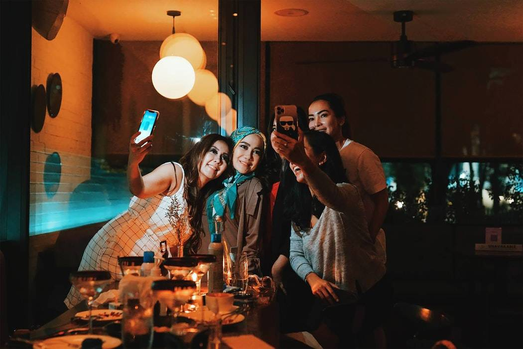 group of girls taking a selfie at a bar
