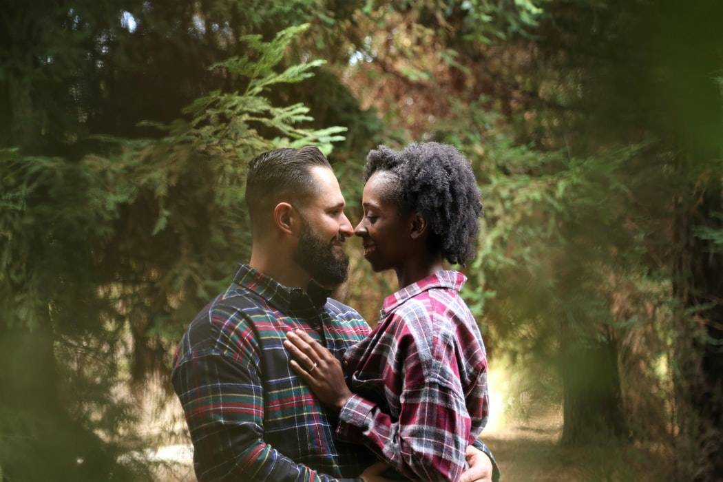 man and woman smiling at eachother and embracing in the forest