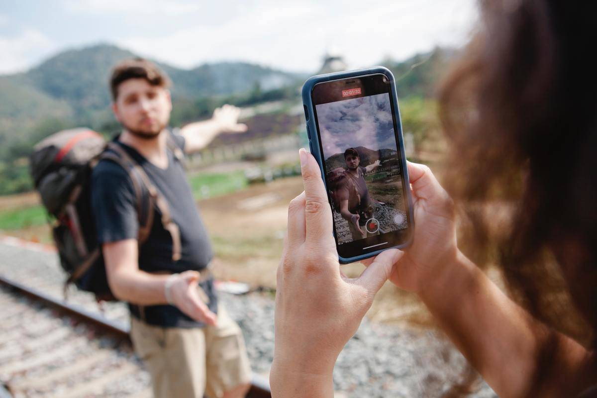 woman taking photo of man while hiking together
