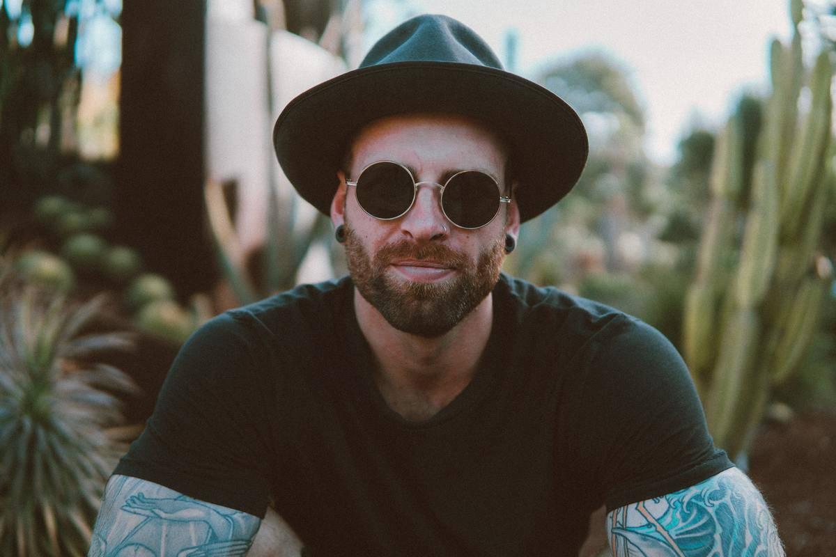 hipster man smiling in fedora and glasses