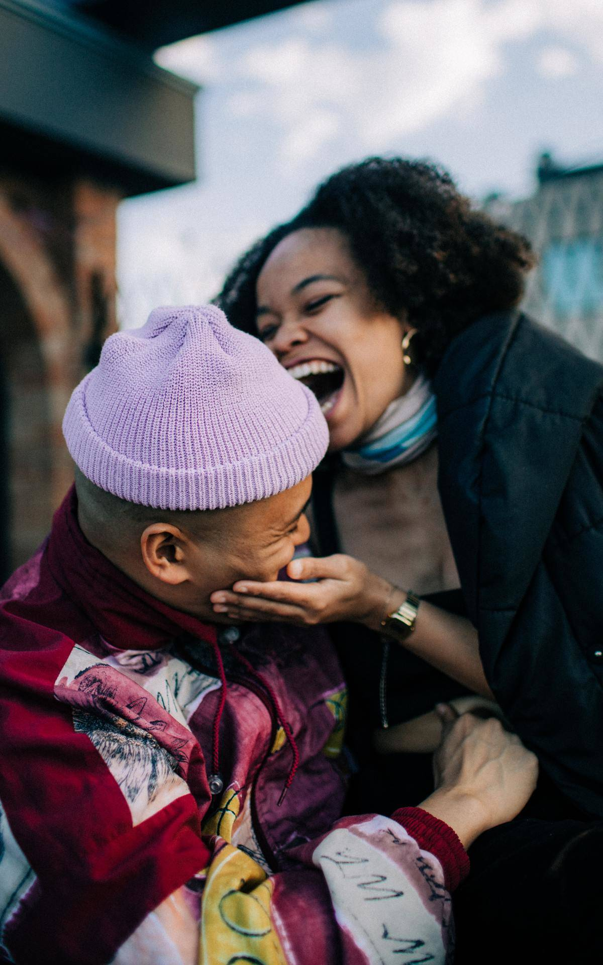 a guy and girl sitting outside laughing together