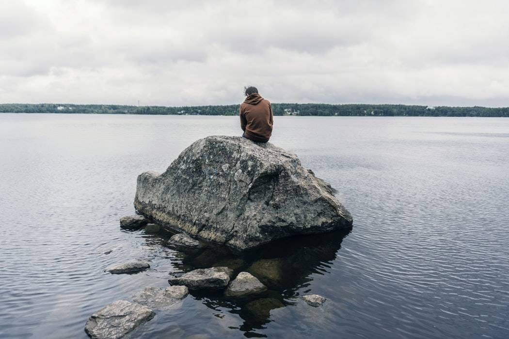 man in a hoodie sitting all by himself on a large rock in the middle of the water staring out at the view