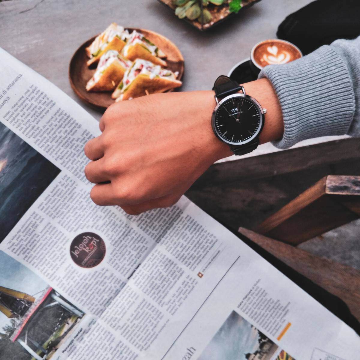looking at watch over table with newspaper and sandwiches