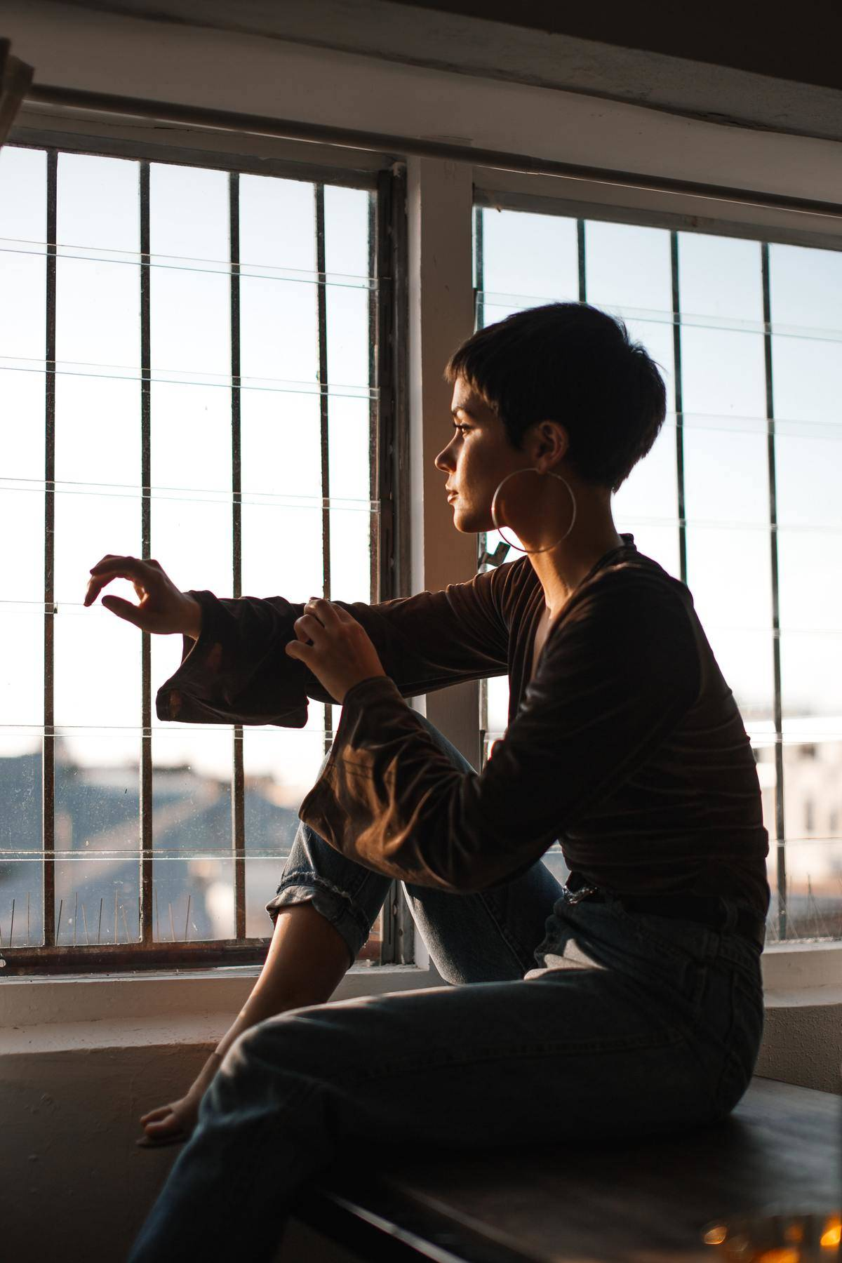 a woman sitting on a table looking out a window