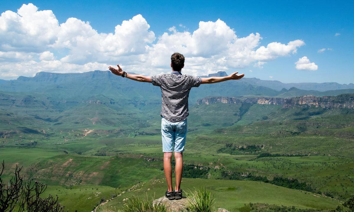 man standing on cliff looking out over valley