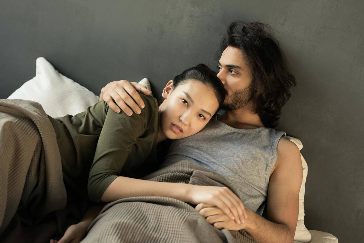 couple lying on a bed together cuddling