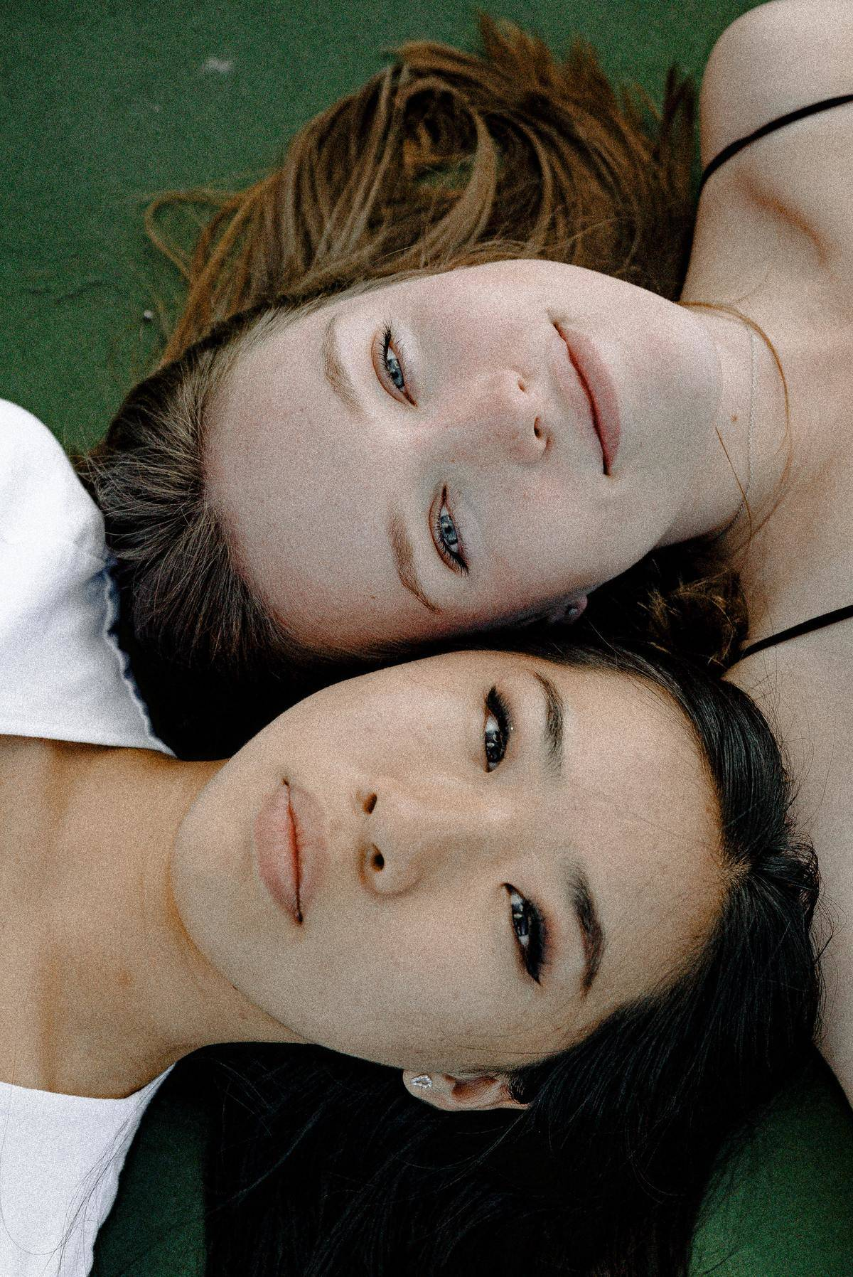two girls lying down with their heads next to each other, looking up