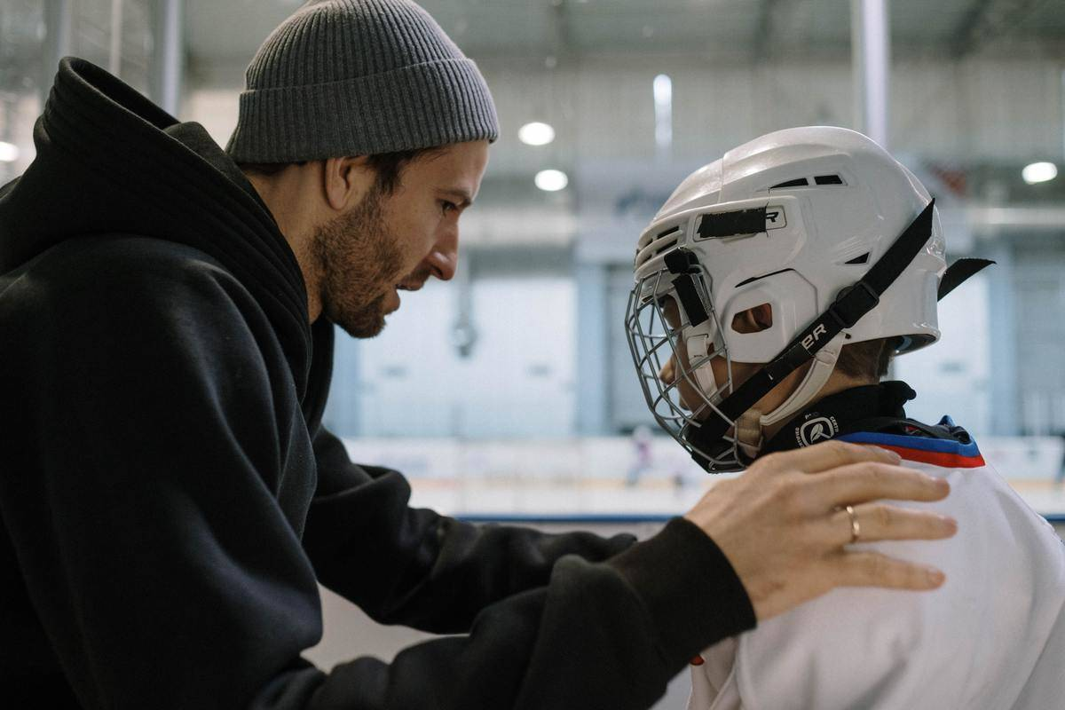 man and boy in front of hockey ring talking