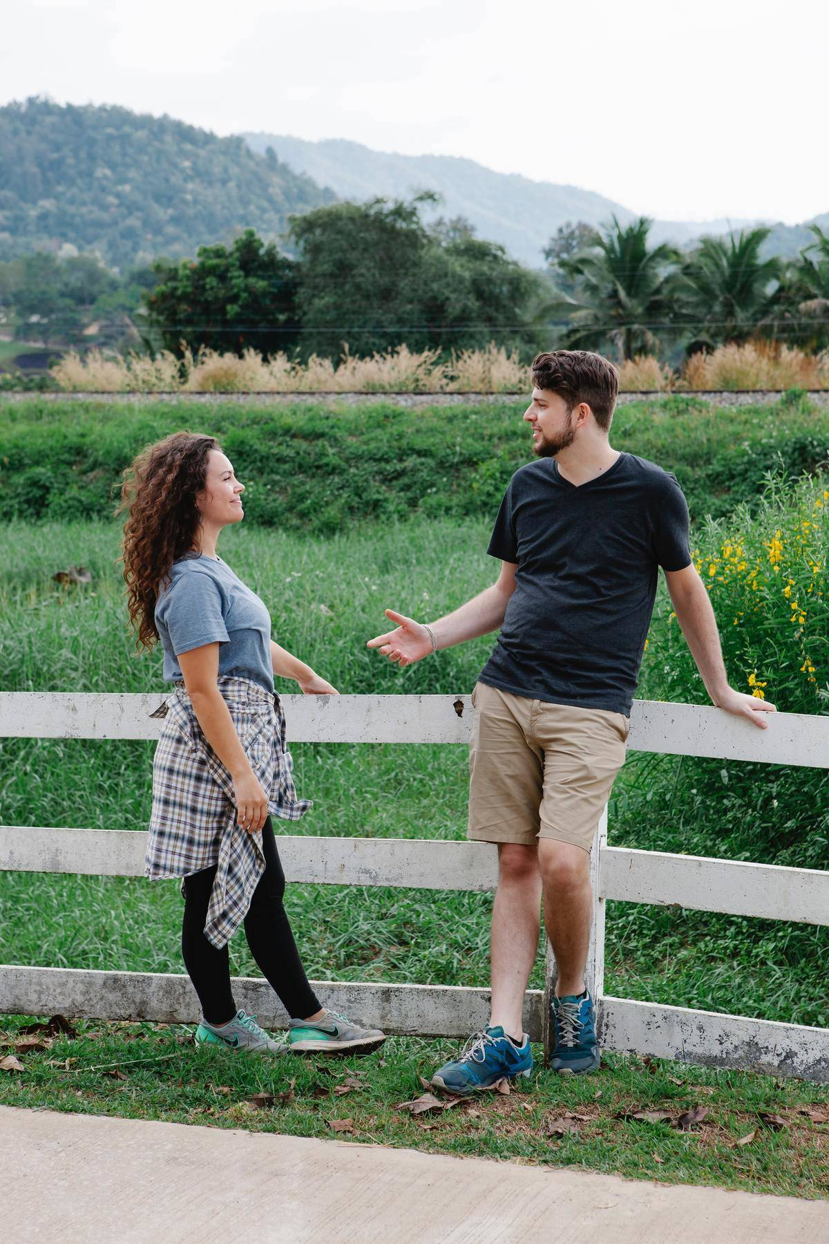 man talks to woman as they stand by a fence
