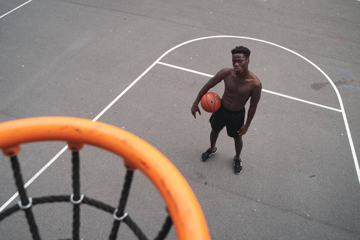 man in basket ball court looking up