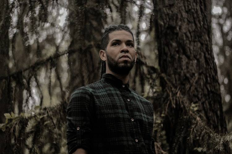 Picture of man in the woods with an unhappy expression on his face