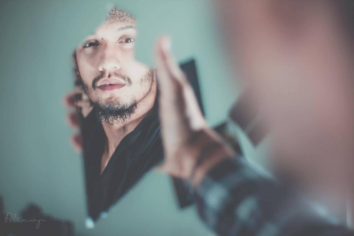 man looking at broken glass reflection of himself