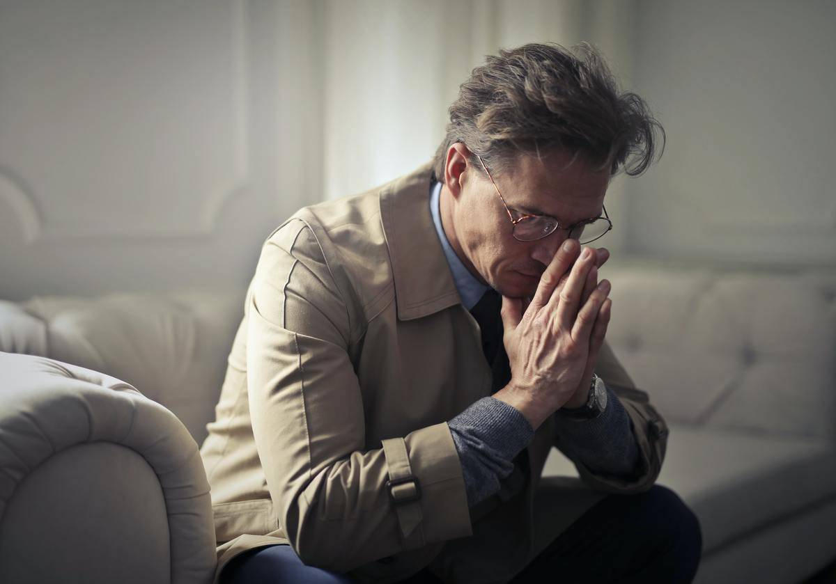 man sitting on couch and looking down in prayer