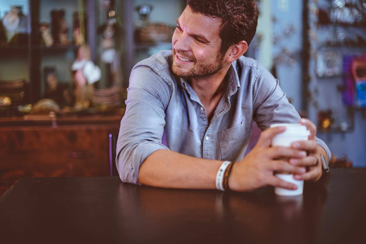 man in blue button down smiling holding coffee