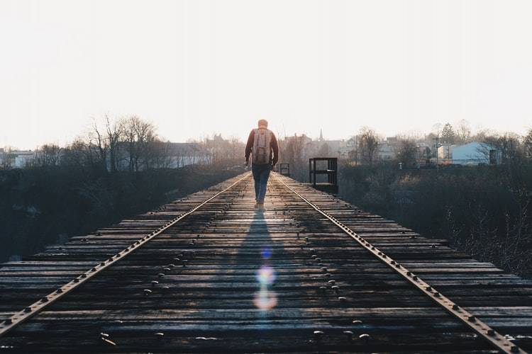 back shot of a man with a large backpack  walking alone on railway tracks