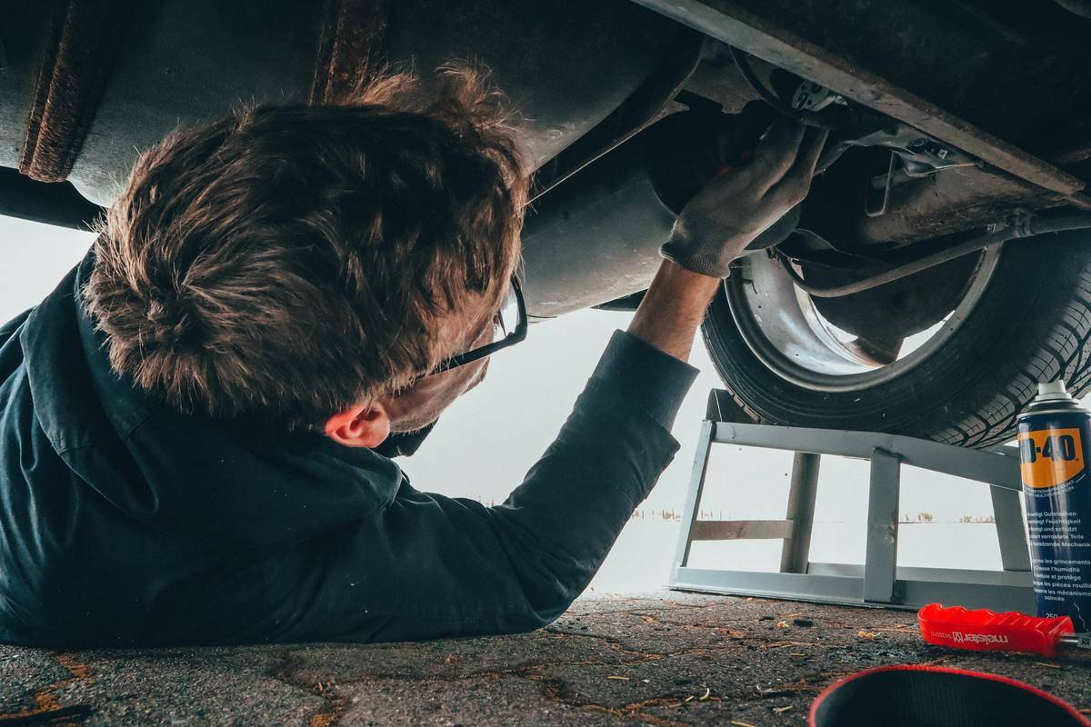mechanic fixing car from under