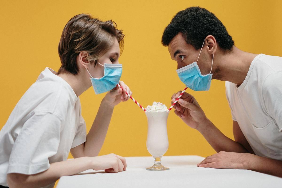 man and woman sharing milkshake while wearing surgical masks