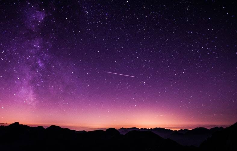 Sublime purple night sky with a shooting star in the middle
