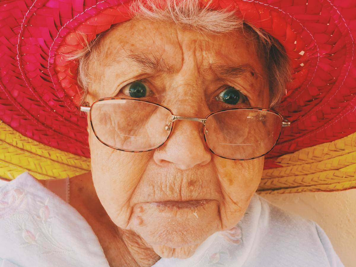 old lady looks angry under her straw hat