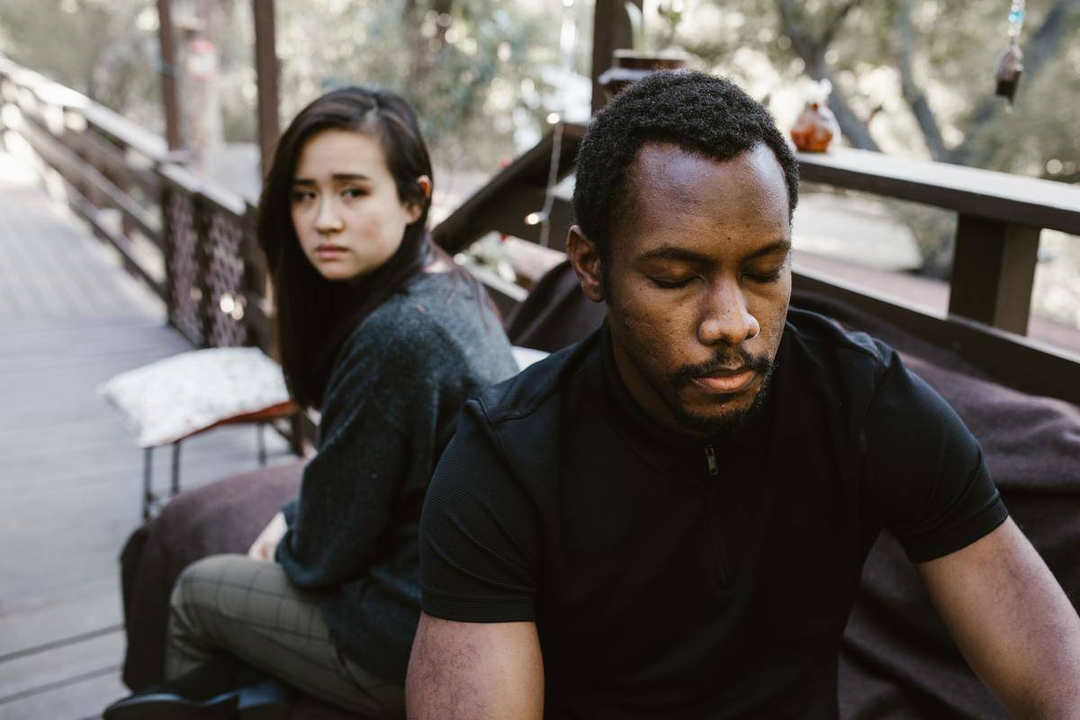 woman looking over her shoulder at man who looks deep in thought
