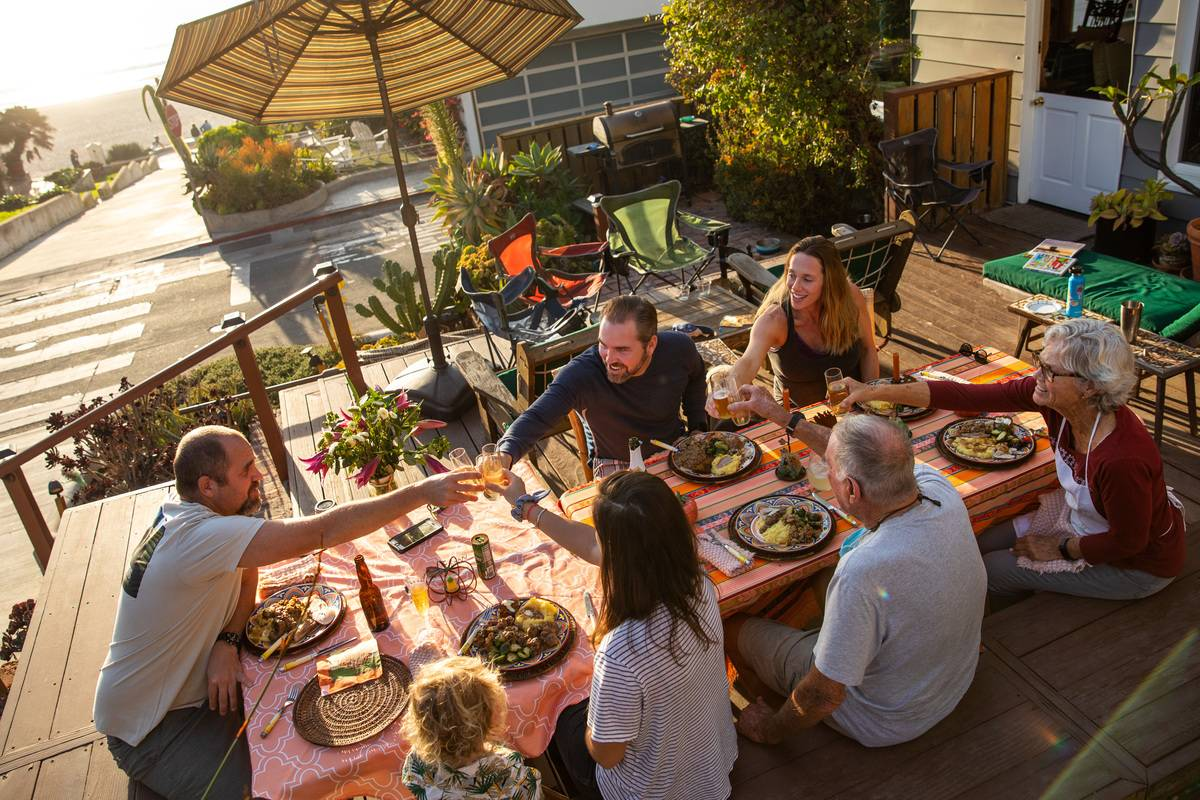 Aaron Liggett, left, makes a toast as Thanksgiving dinner is served, spending it with, clockwise from Aaron, brother Austin and his wife Nina, parents David and Robin Liggett and his wife Michelle and son Waylon, outside his parents home on 9th Street in Manhattan Beach