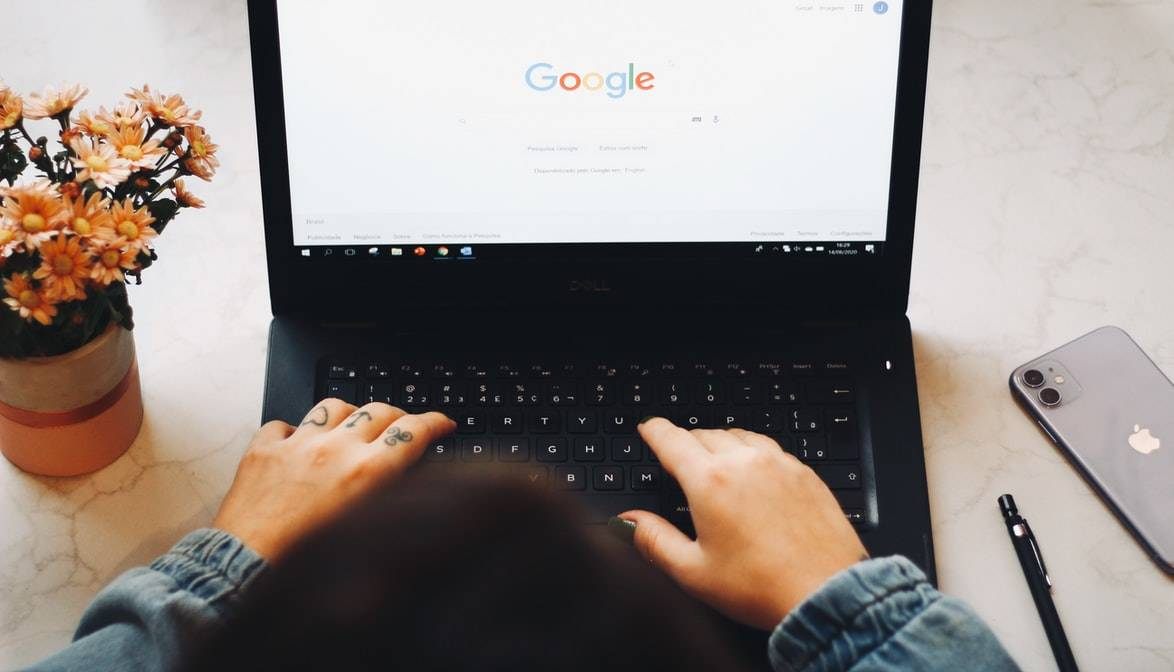 person using google search engine on their computer as they type something in
