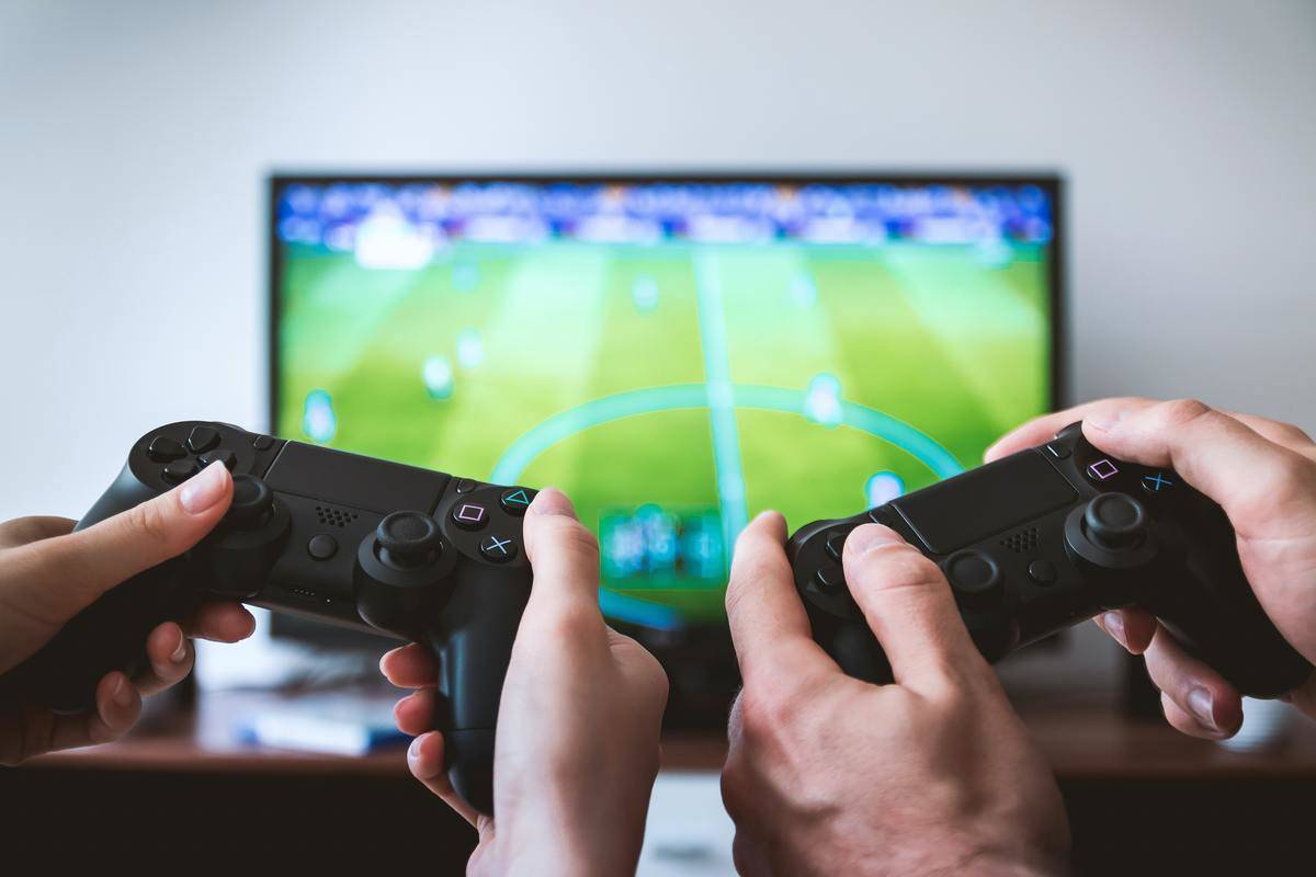 two hands playing fifa on playstation