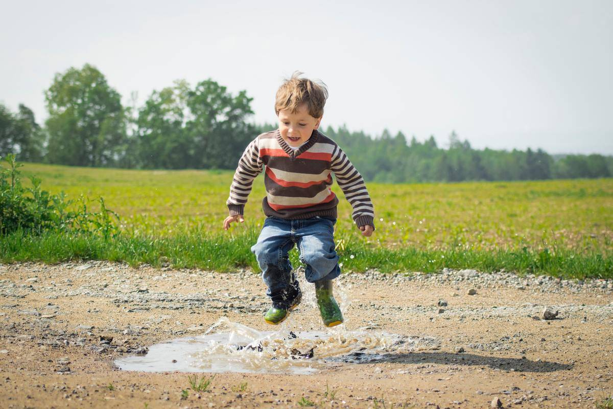 boy jumping in muddy puddle