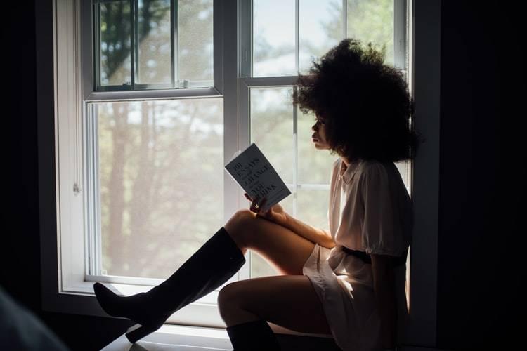 woman reading book on windowsill