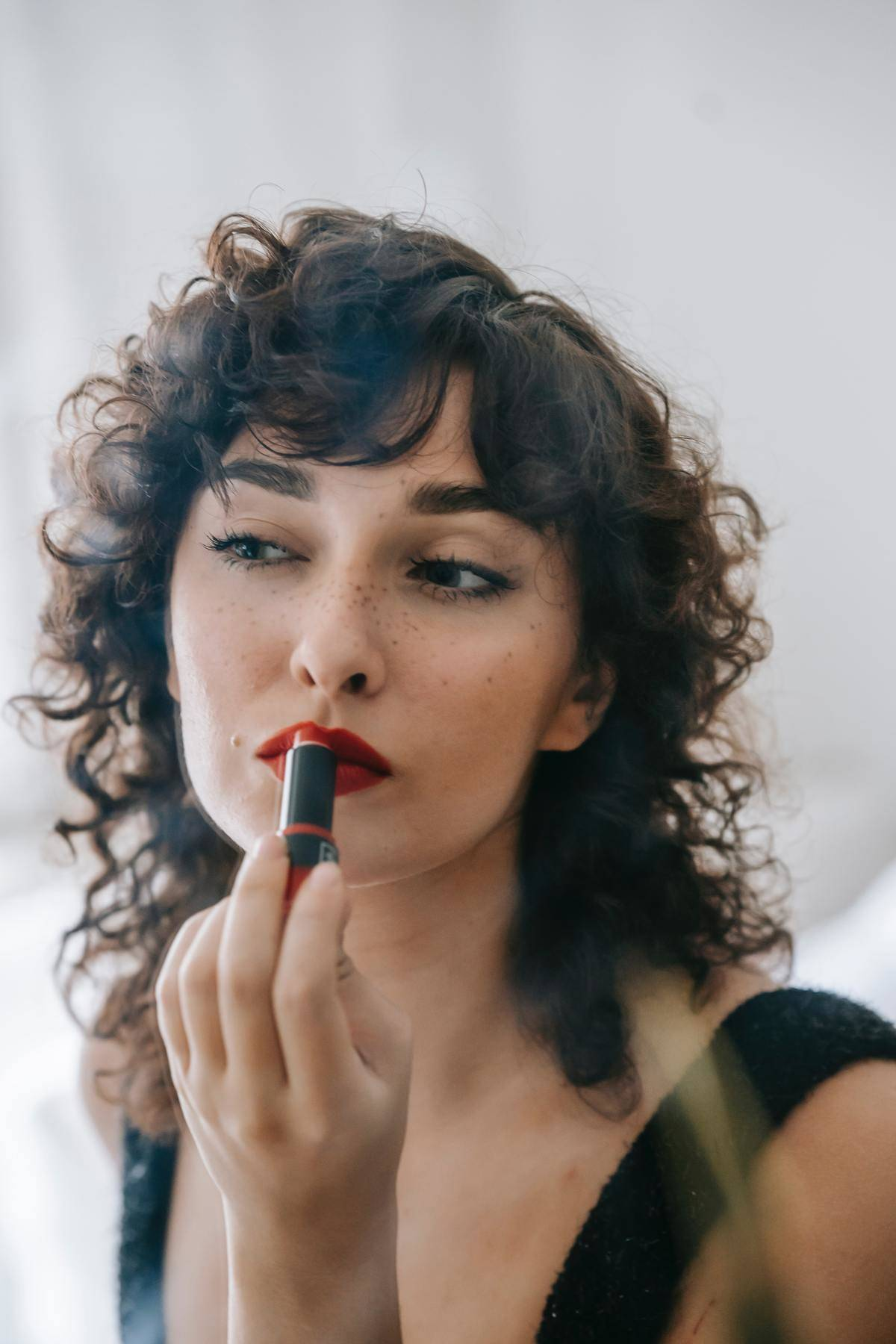 a woman looking in the mirror putting on red lipstick