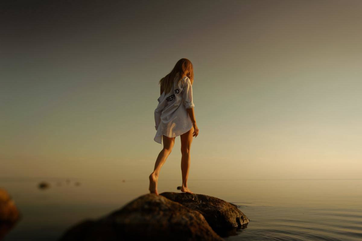 woman standing alone on rock in body of water