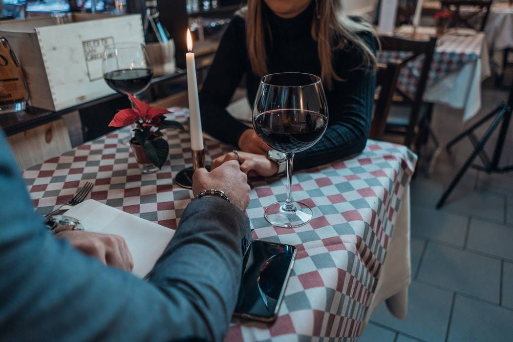 man and woman holding hands at dinner table at restaurant with red wine and a candle on the table