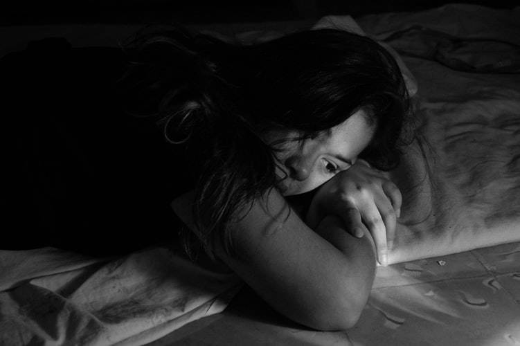 black and white photo of a woman lying in bed on her stomach staring dow