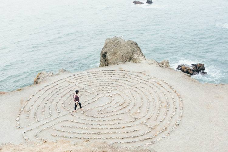 person standing in the middle of a maze in the sand