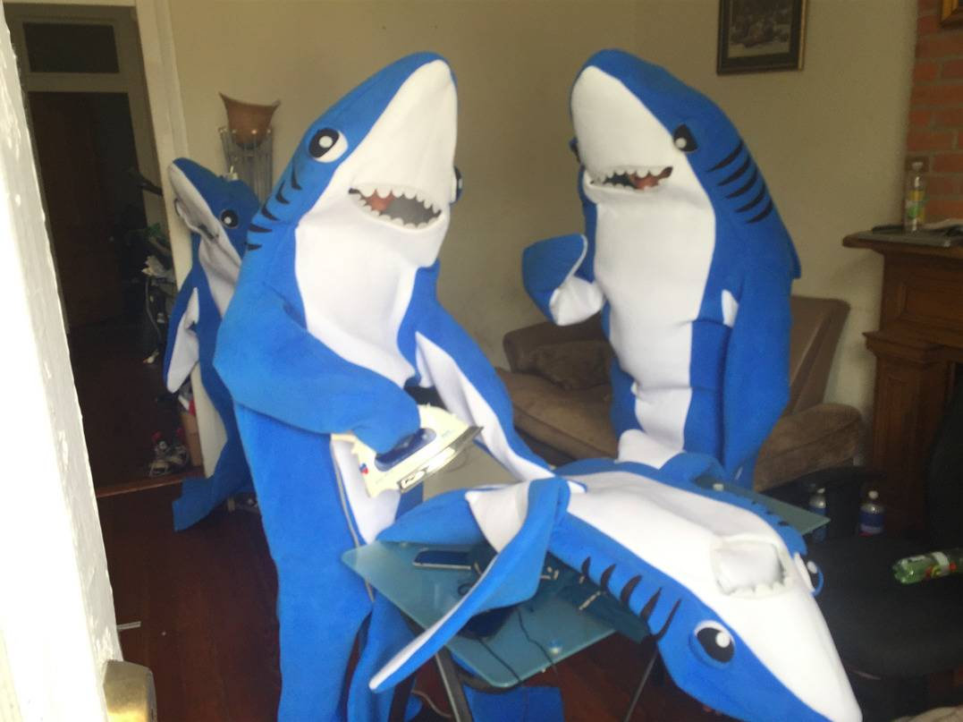 Two people in shark costumes ironing a third shark costume