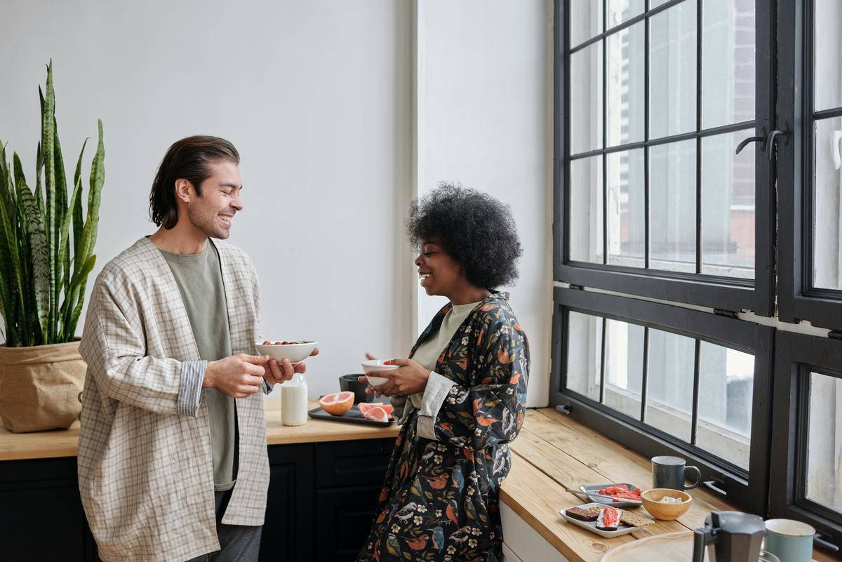 two people standing in a kitchen talking with one another