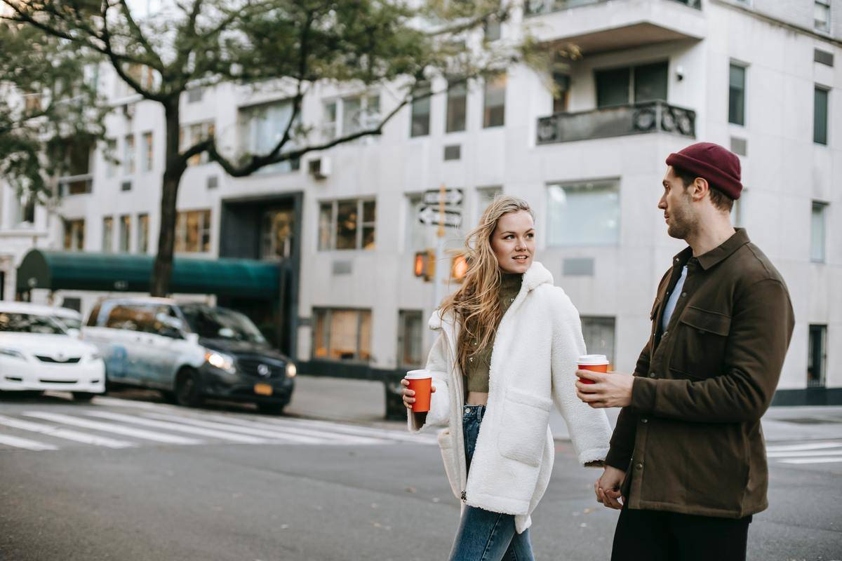 a guy and girl crossing the street holding some coffee cups