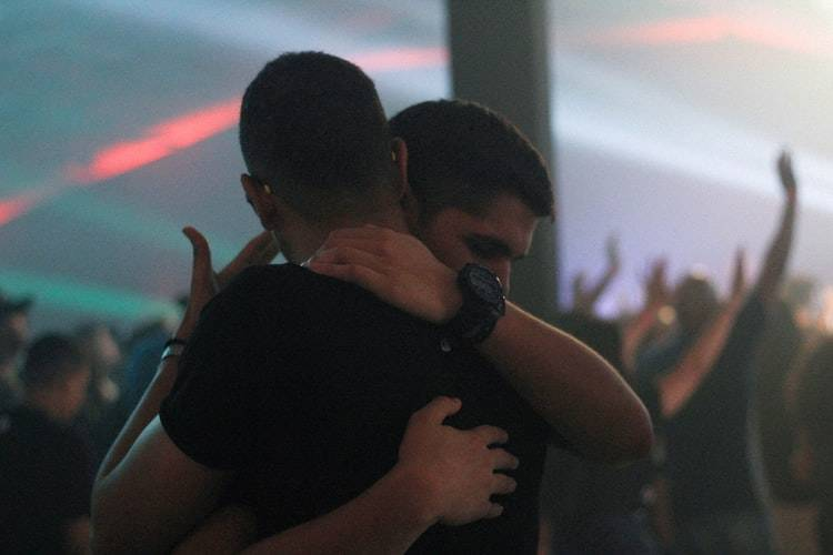 two men embracing at a club
