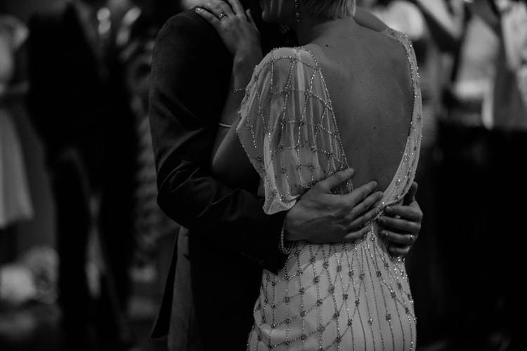 black and white shot of the upper bodies of two people in fancy clothing who are closely slow dancing together