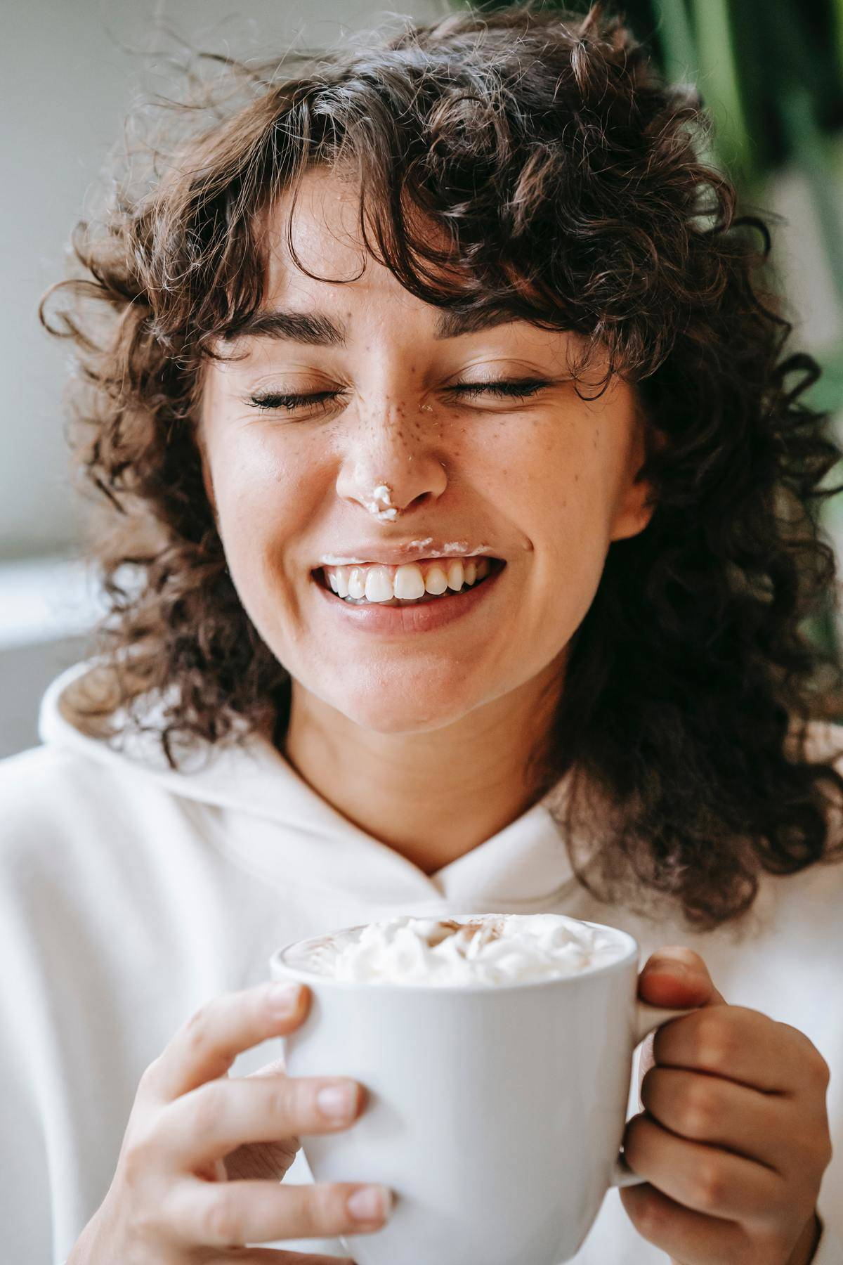 a woman holding a coffee cup while smiling with whipped cream on her nose